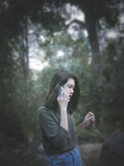 Young woman talking on phone at forest
