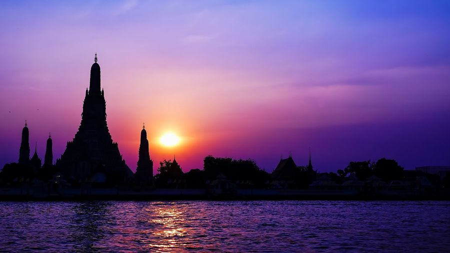 Silhouette temple by building against sky during sunset