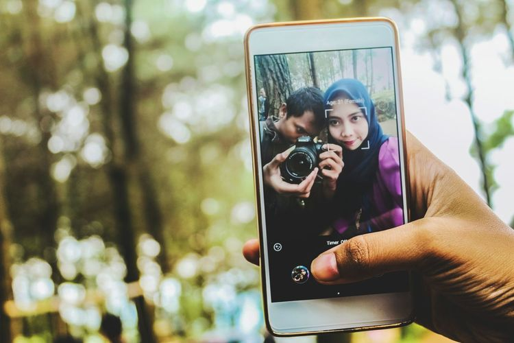 Close-up of woman photographing through mobile phone outdoors
