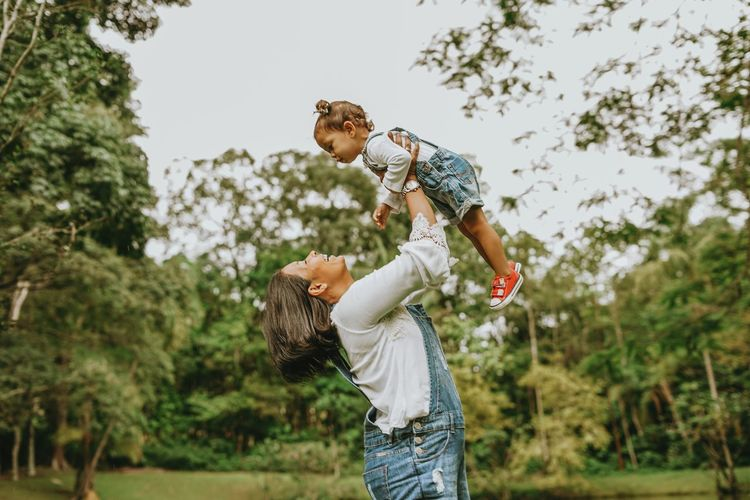 Side view of mother holding daughter mid air while standing at park