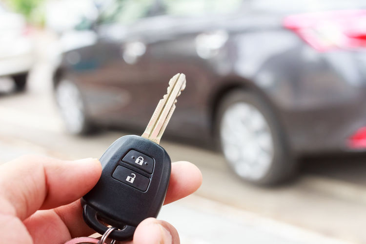Close-up of man holding car key