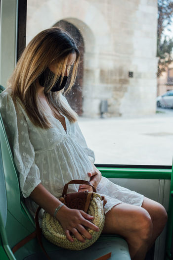 Pregnant woman with face mask making a trip on a city bus.