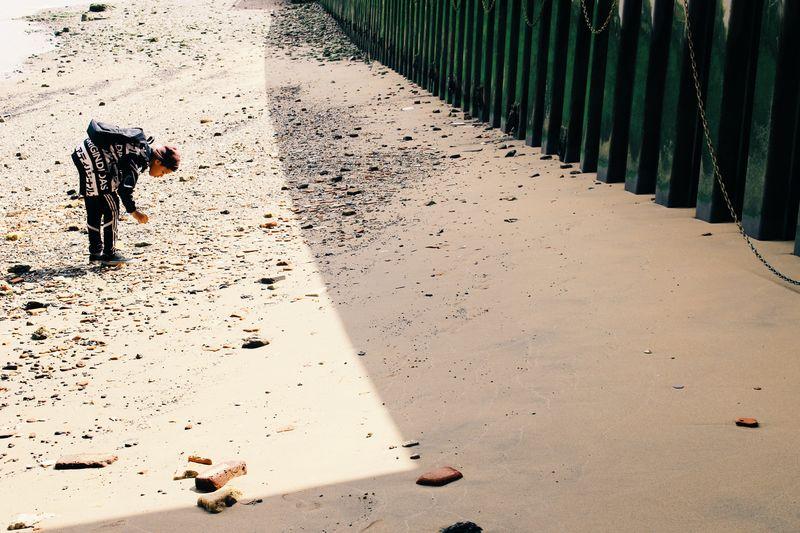 Side View Of Teenage Boy Bending At Beach