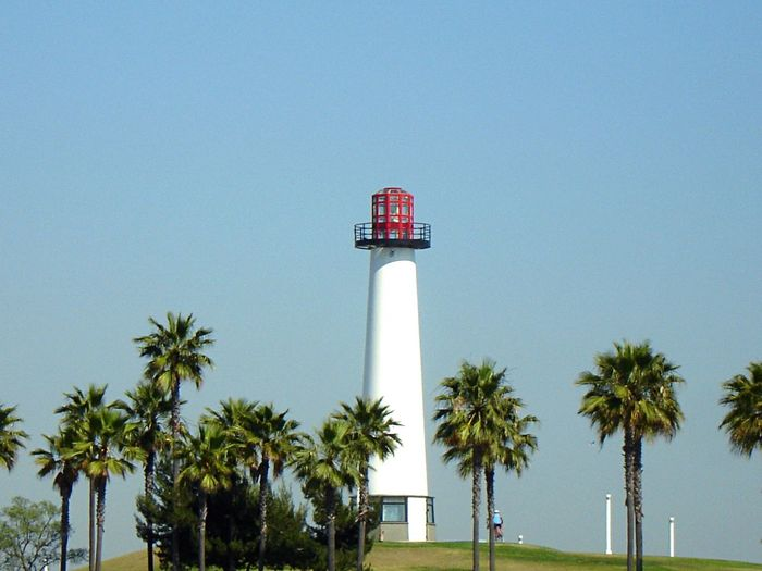 View of lighthouse and palm trees against blue sky