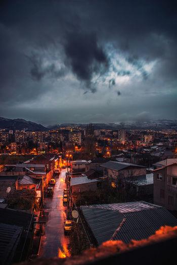 Illuminated cityscape against cloudy sky at dusk