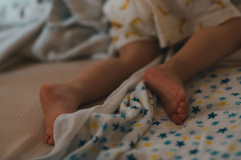 Midsection of child lying on bed