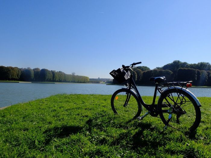 Bicycle on field by lake against clear sky