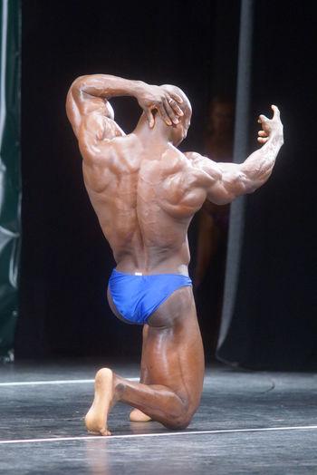 Rear View Full Length Of Shirtless Body Builder