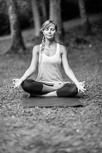 Young woman meditating in lotus position at park