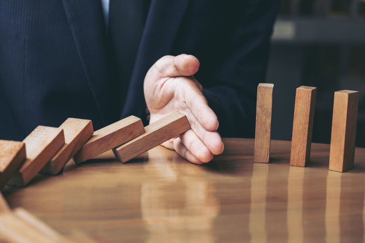 Adult Analysis Block Building - Activity Businessman Close-up Day Finance Human Body Part Human Hand Indoors  Investment Marketing Men Occupation One Man Only One Person People Riskybusiness Stop Strategy Wood - Material Wooden Wooden Block Wooden Game
