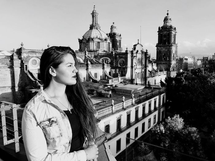Young woman looking away while standing against cathedral in city