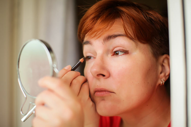 Close-up of woman applying eyeliner while looking at mirror at home