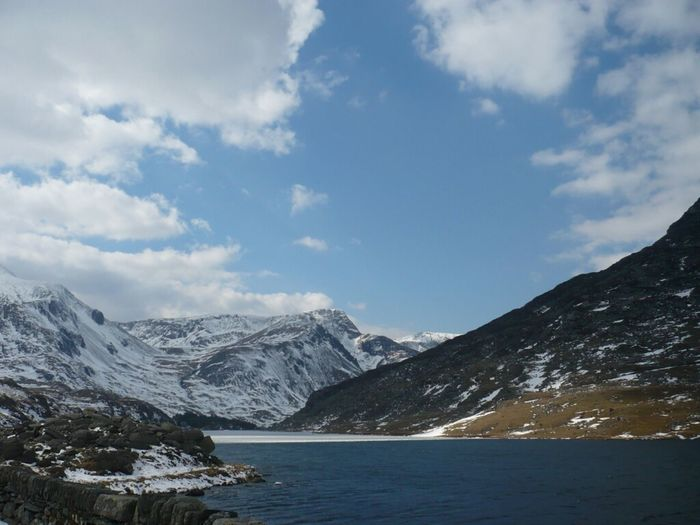 Scenic view of lake by snow covered mountains against sky