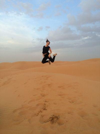 Full length of woman jumping on sand dune
