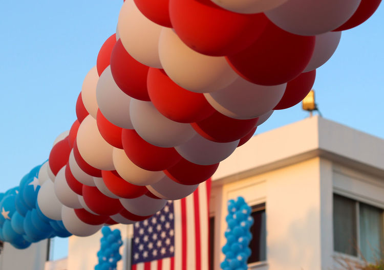 Low angle view of balloons by building with american flag