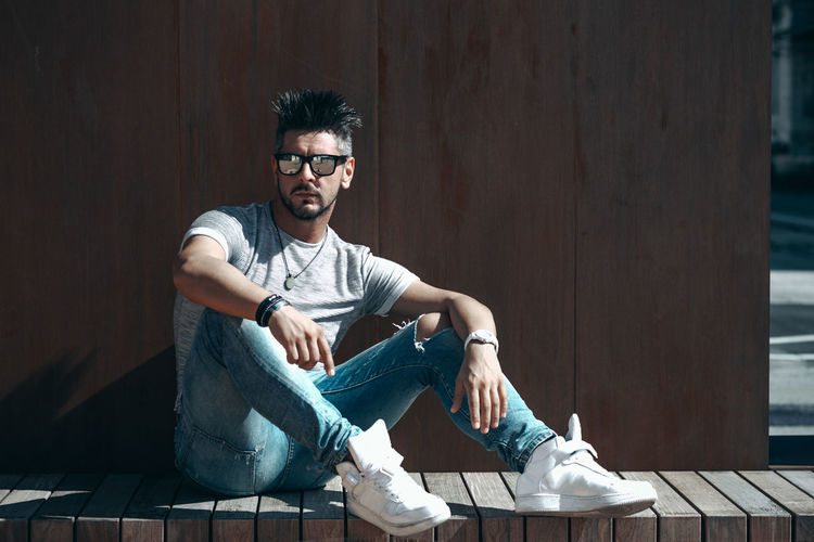 Sitting Casual Clothing Young Adult Young Men Full Length Glasses One Person Eyeglasses  Front View Leisure Activity Real People Wood - Material Looking At Camera Day Lifestyles Men Relaxation Sunlight Jeans
