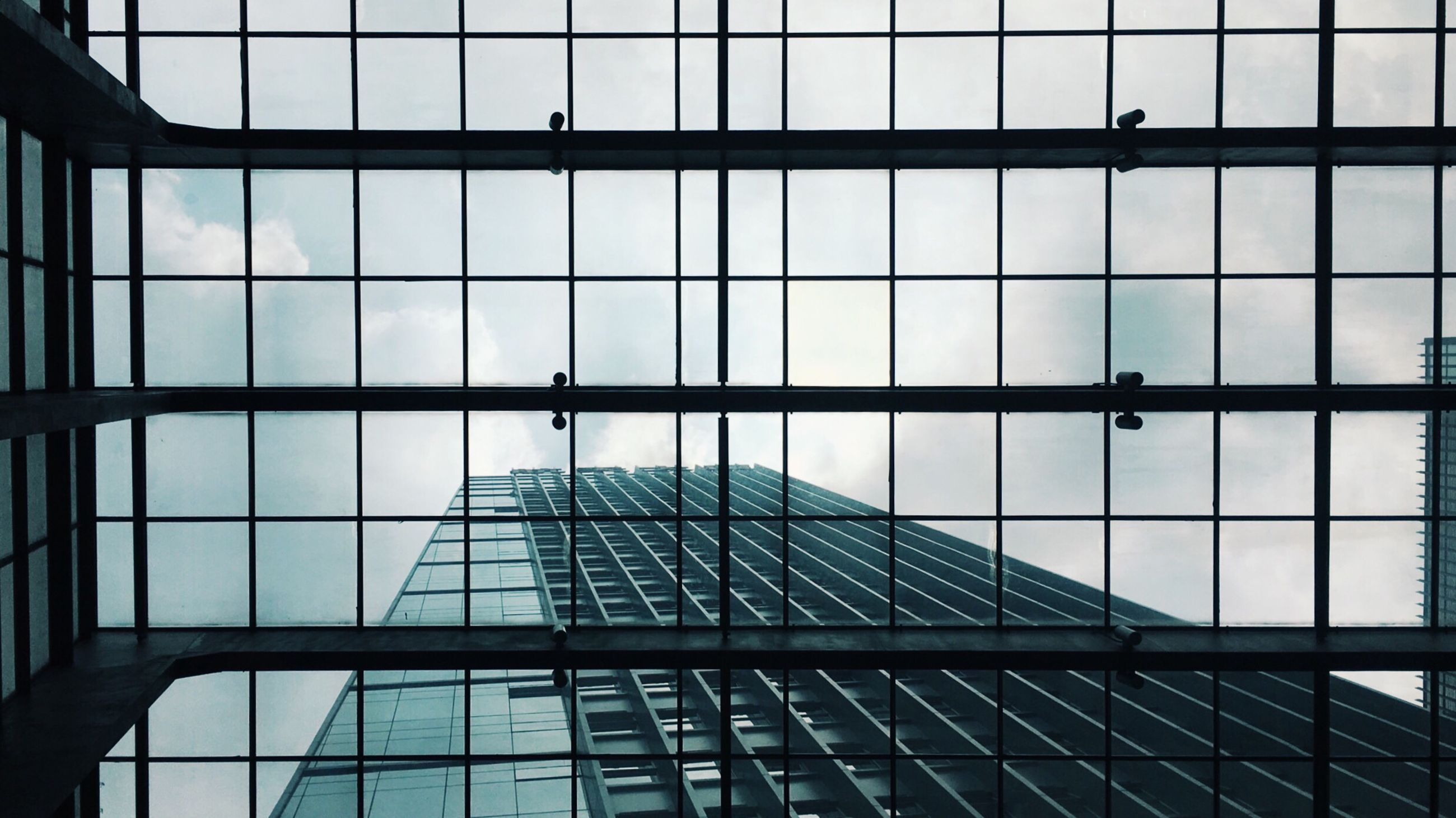 architecture, indoors, glass - material, built structure, low angle view, transparent, square shape, modern, geometric shape, ceiling, sky, directly below, skylight, full frame, office building, day, architectural feature, repetition, cloud - sky, skyscraper, no people
