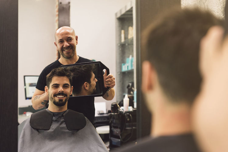 Barber holding mirror while showing to customer in salon