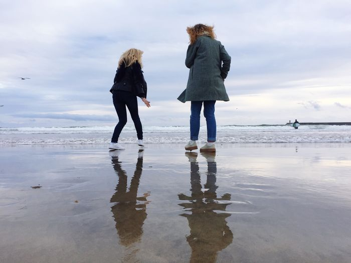 Rear view of women walking on wet shore at beach