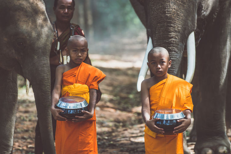 Monks standing with elephant in forest