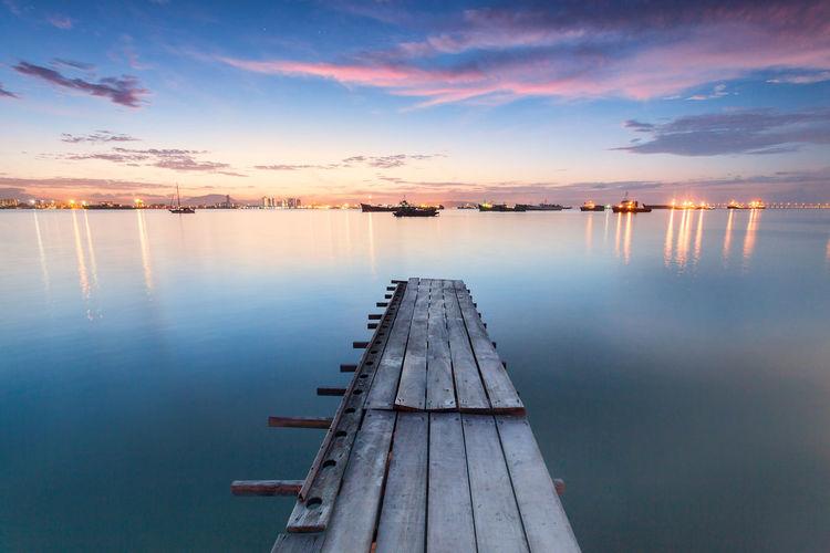 Pier Over Lake Against Sky During Sunset