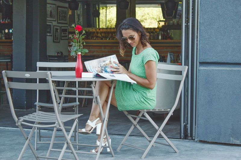 Side View Of Mid Adult Woman Reading Magazine While Sitting On Chair At Sidewalk Cafe