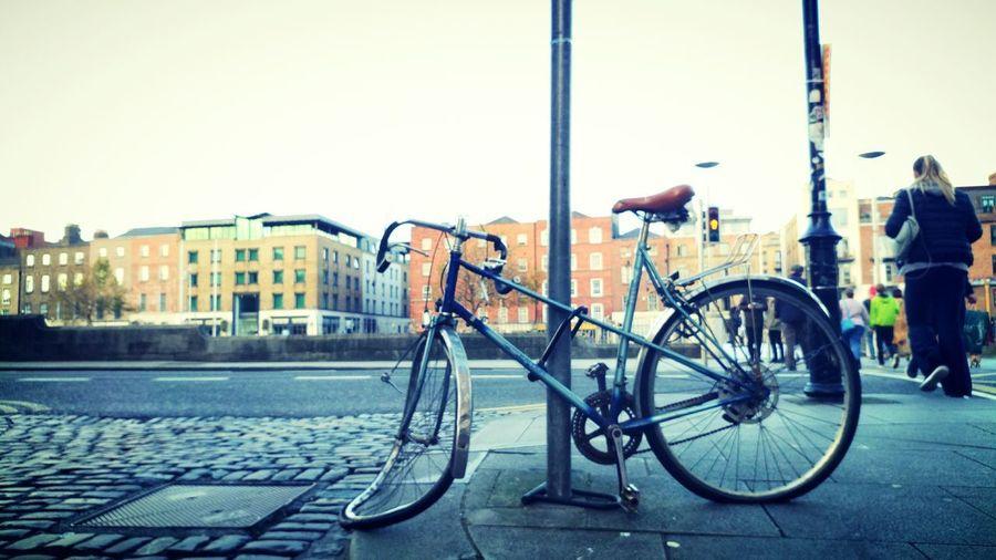 Bicycles on bridge in city against sky