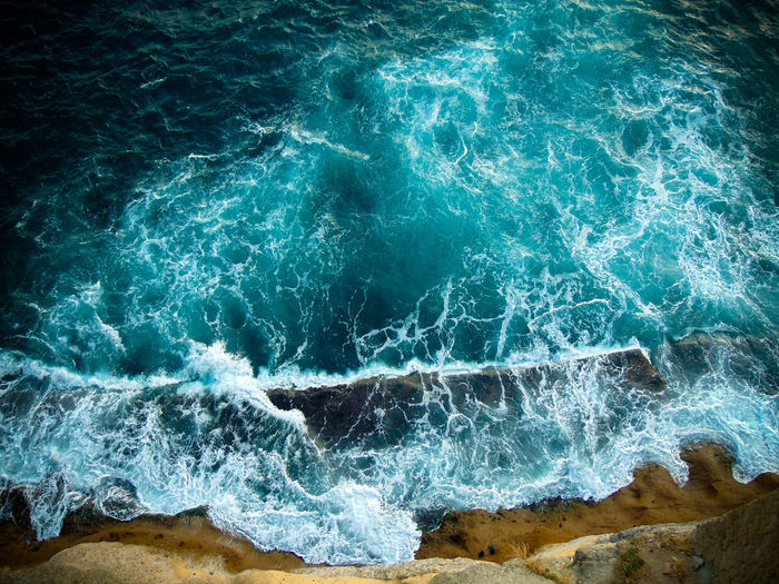 Aerial view of sea wave crashing on shore