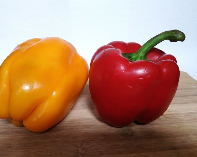 Paprika yellow and red on a wood table Yellow Pepper Wood Wooden Plate Table Healthy Eating Healthy Food Red Red Bell Pepper Fruit Vegetable Healthy Lifestyle Table Bell Pepper Raw Food Paprika Yellow Bell Pepper Pepper - Vegetable Two Objects Things That Go Together