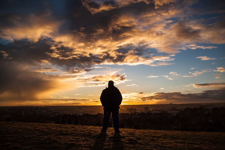Rear view of silhouette man standing on field against cloudy sky