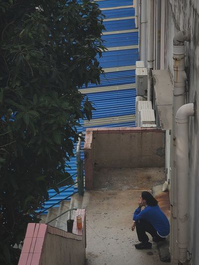 Rear view of man sitting outside building