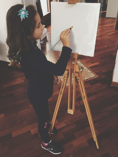 Girl Painting While Standing On Hardwood Floor