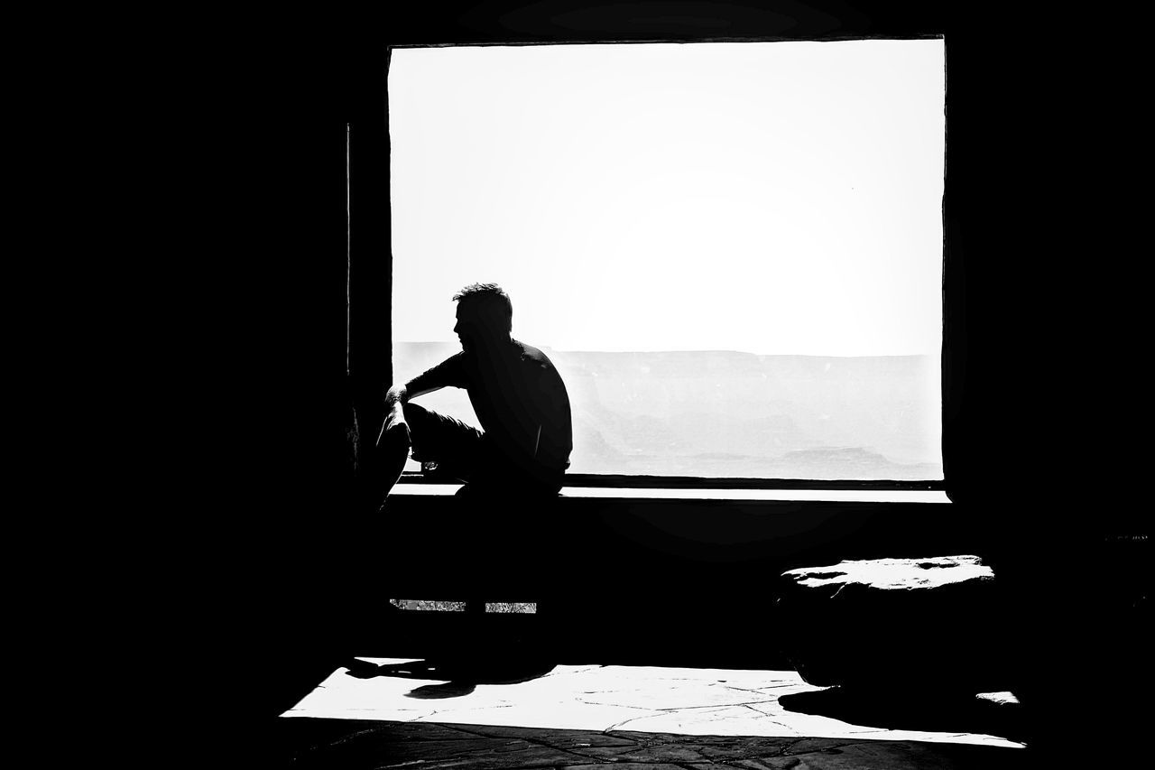 Silhouette man in front of window at home
