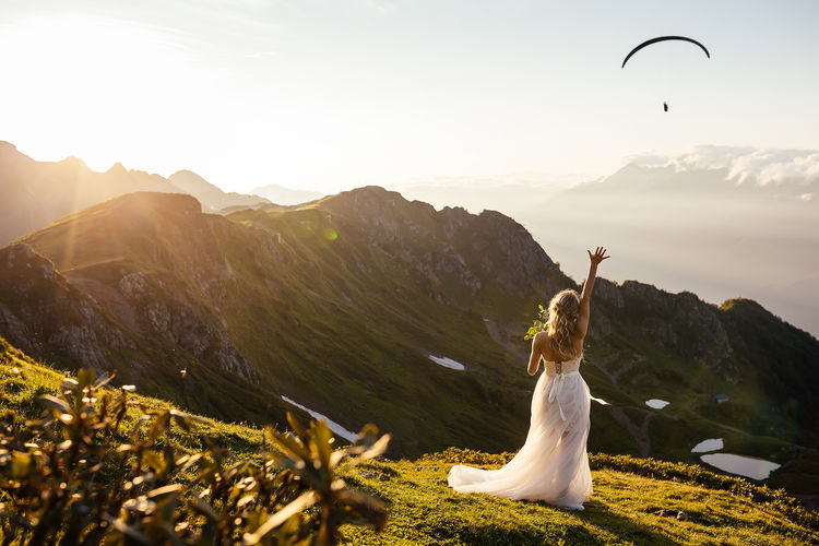 Rear view of bride with hand raised standing on land against mountains during sunset