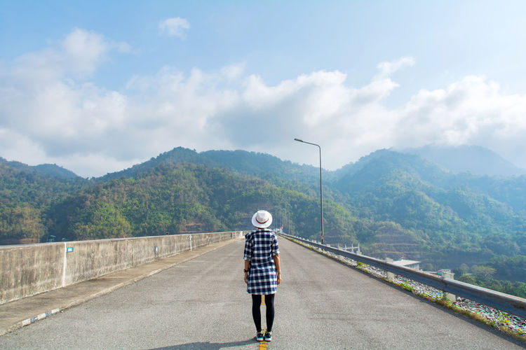 One Person Rear View Cloud - Sky Sky Real People Mountain Transportation Full Length Casual Clothing Road Day Nature Lifestyles Adult The Way Forward Standing Direction Leisure Activity Walking Mountain Range Outdoors Travel Tourism Tourist Women Sad Happiness Funny Relaxing Alone Looking Landscape Dam Nature Freedom