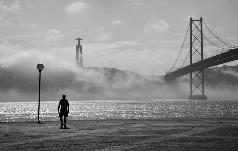 Silhouette man standing on street by tagus river and april 25th bridge against sky during foggy weather