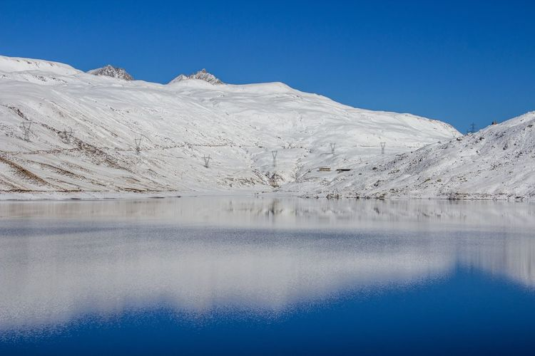 Scenic view of snow covered mountains with reflection on lake against clear blue sky