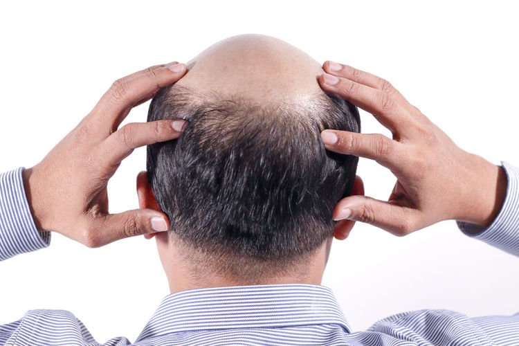 Rear view of man with hands on head against white background