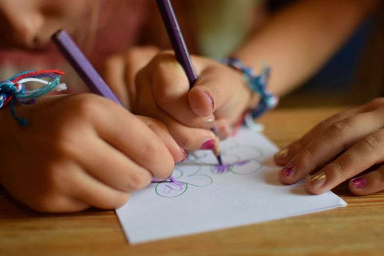 Close-up of siblings drawing in paper on table