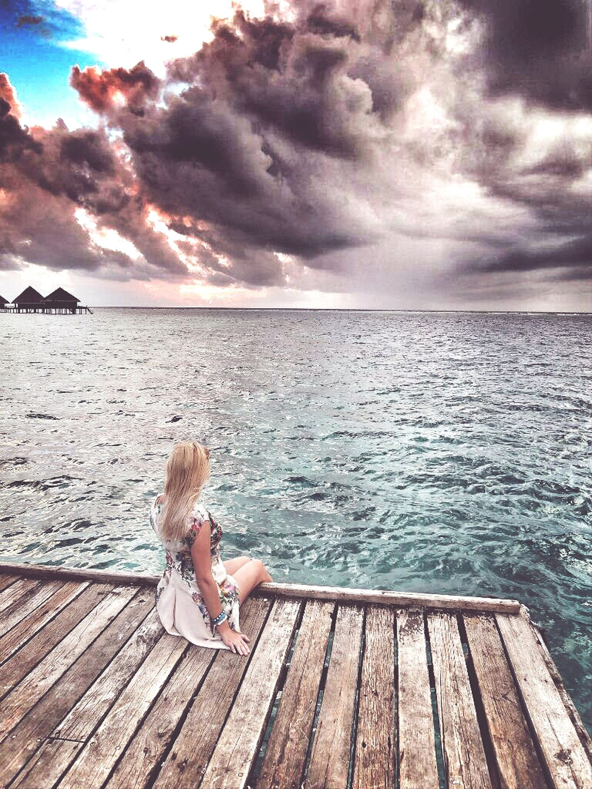 water, sky, sea, lifestyles, leisure activity, tranquil scene, scenics, tranquility, pier, horizon over water, full length, cloud - sky, rear view, sitting, relaxation, beauty in nature, wood - material, idyllic