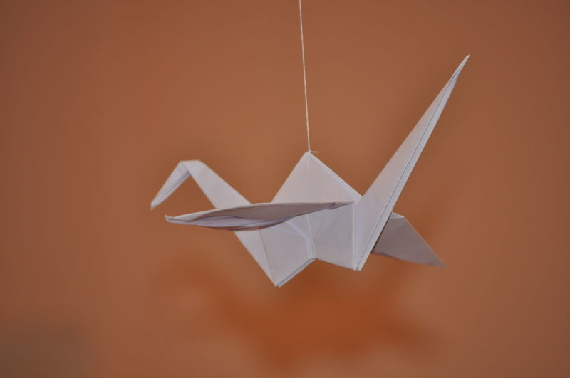 Close-up of origami hanging against orange wall