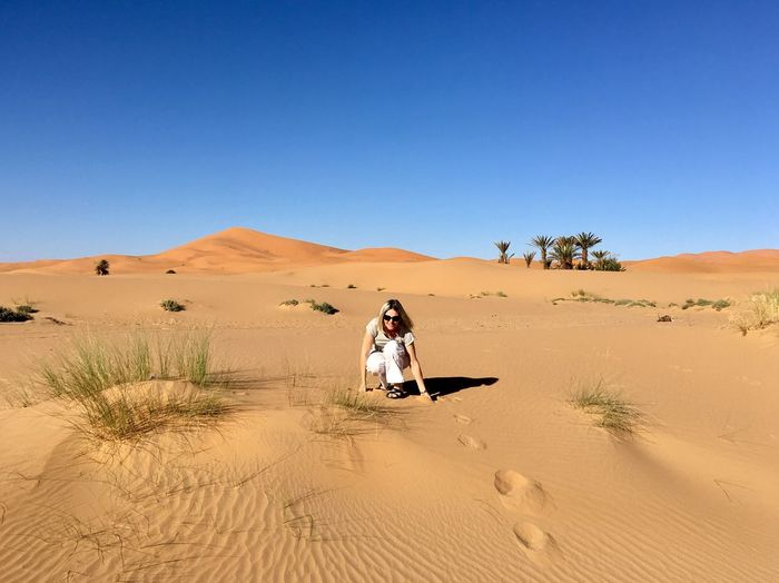 Portrait of woman crouching at desert against clear sky