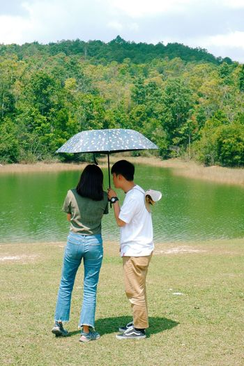 Rear view of couple standing by lake during rainy day