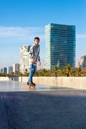 Full length of man jumping against buildings in city