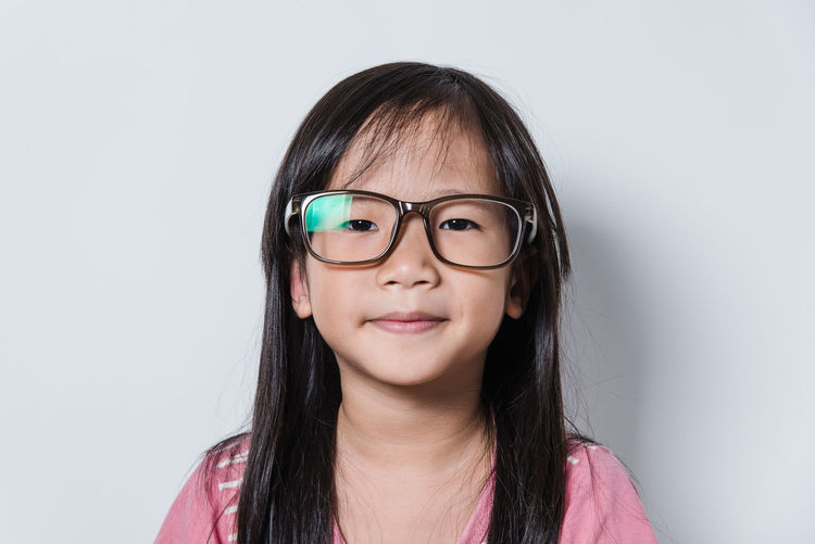 Portrait of girl wearing eyeglasses against white background