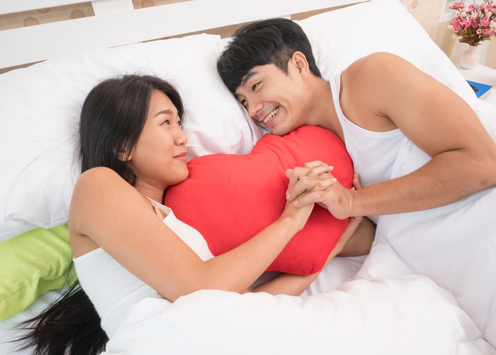 High Angle View Of Couple With Heart Shape Pillow Lying On Bed At Home
