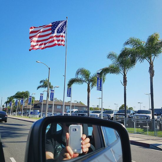 Car Transportation Mode Of Transport Flag Land Vehicle Day Patriotism Outdoors Sky Reflection Cellphone Photography PCH Human Hand InMotion RADIOFREQUENCY Theknowledge