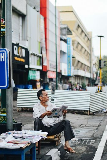 Man selling newspapers in city