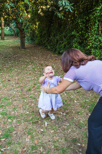 mother and little dauther Adult Bonding Casual Clothing Child Childhood Daughter Day Family With One Child Females Full Length Girls Grass Mother Outdoors People Standing Togetherness Tree