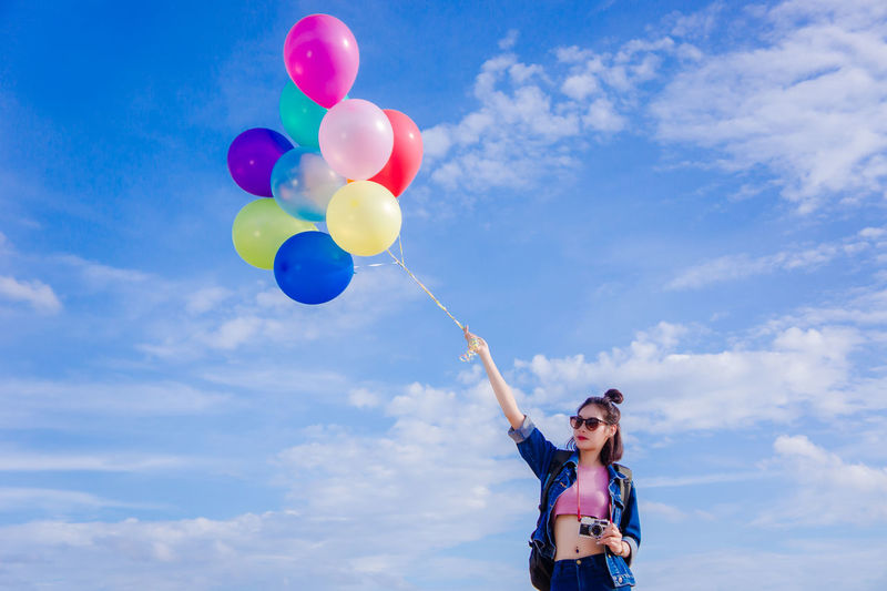 A day Happy People Balloon Beautiful Woman Casual Clothing Cloud - Sky Day Freedom Front View Happiness Helium Balloon Holding Human Arm Leisure Activity Lifestyles Low Angle View Multi Colored Nature One Person Outdoors Real People Sky Standing Women Young Adult Young Women